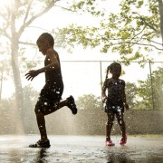 Children run through a sprinkler system installed inside a playground to cool off during a hot summer day in New York